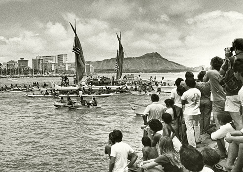 Black and white photograph, the Hōkūle'a voyaging canoe coming into harbor after its inaugural voyage as spectators watch.