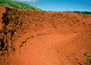 A depression of rust-colored earth, the result of soil erosion, is pictured. In the background are green grass and trees, and blue sky.