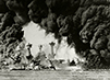 In this black and white photograph, battleships are surrounded by black smoke during the attack on Pearl Harbor.