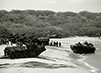 Black and white photograph of tanks and APC's landing on beach for military exercises.