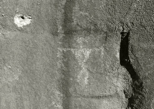 In this black and white photograph, a bullet hole is seen right above an ancient drawing of a person on a rock wall.