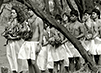 A procession of people participating in the Makahiki ceremony stand amongst trees. Each person wears a white skirt and many carry ceremonial objects.