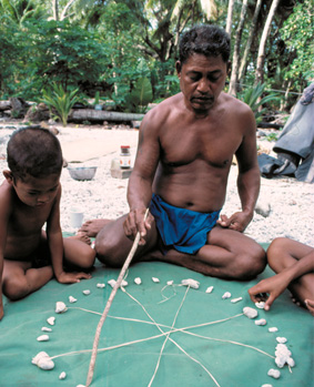 Micronesian wayfinder, Mau Piailug, uses a star compass to teach navigation to his son and others.