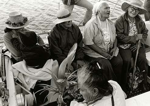 Black and white photograph of a group of 4 elderly people and a younger woman holding a baby sit on a boat headed for Kaho'olawe.