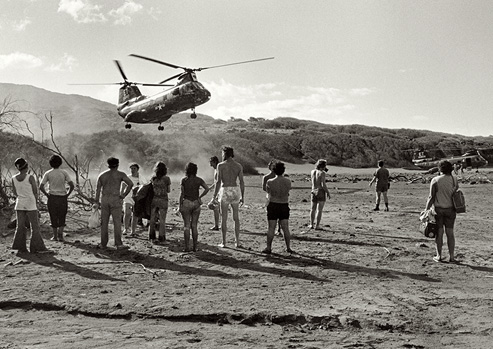Black and white photograph of a military helicopter descends on a group of occupiers on Kaho'olawe.