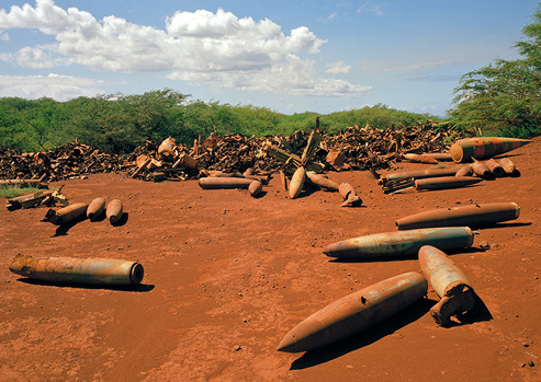 Artillery is scattered across the rust-colored, dirt-covered ground.