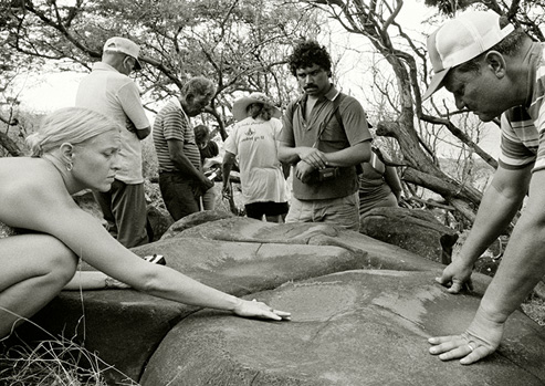 7 people stand around an adze grinding stone on Kaho'olawe. A woman and man in the foreground touch the stone, white the rest stand a small distance from it. Trees are in the background. This is a black and white photo.
