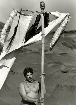 Black and white photograph of a shirtless man underneath a t-shaped pole made of wood with fabric draped across.