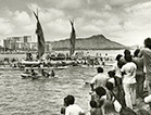 Black-and-white photograph of Hōkūle'a voyaging canoe returning from its first voyage to Tahiti in 1976. Spectators watch the Hōkūle'a coming into harbor as other canoes surround it.