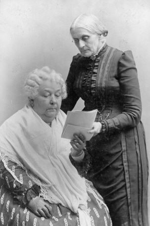 An old White woman sits and reads a pamphlet, another old White woman stands over her left shoulder.