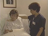 White female nurse in blue scrubs, speaks to an elderly White woman in a hospital bed..