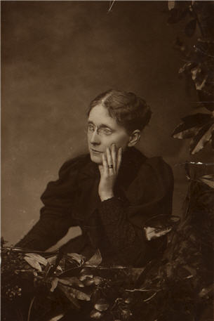 A woman seated with her left hand on her left cheek, and looking to her right.