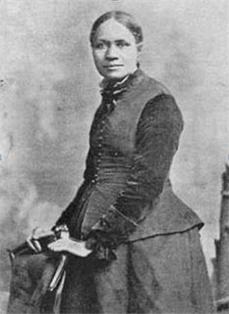 A young woman stand with her hands on a back of a chair.