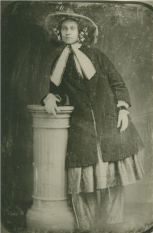 A woman leans on a pedastal to her right, wearing a brimmed hat and pants beneath a skirt and a coat.