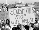 Crowd with signs of 'Rapists must be stopped!,' and 'Sexism Kills Stop Wife Abuse'