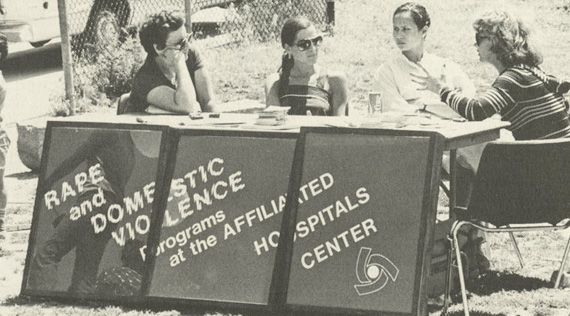 Four women sitting at a table with identifying sign.
