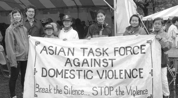 Asian American adults and children stand holding a banner and looking at the viewer.