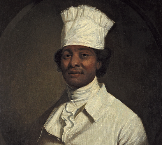 African American man wearing all white, including a white cylindrical cook's hat.