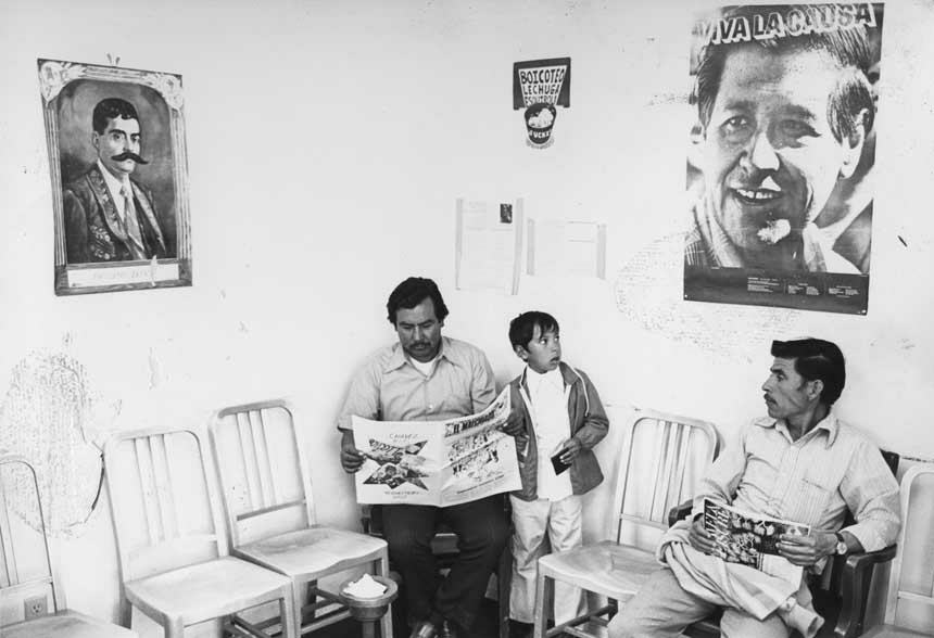 Two Latino men and one child in a clinic waiting room. The two men are seated and reading.