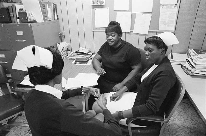 Three African American women sit around a desk; two are wearing nursing caps.