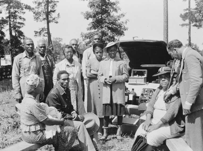 10 African American men and women wait as seated woman receives treatment from a doctor.