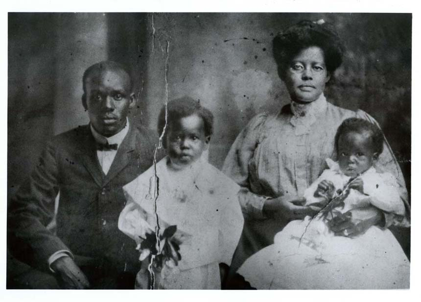 Photo of African American father, mother, and two young sons. Dr. Berry second from left at age 5.