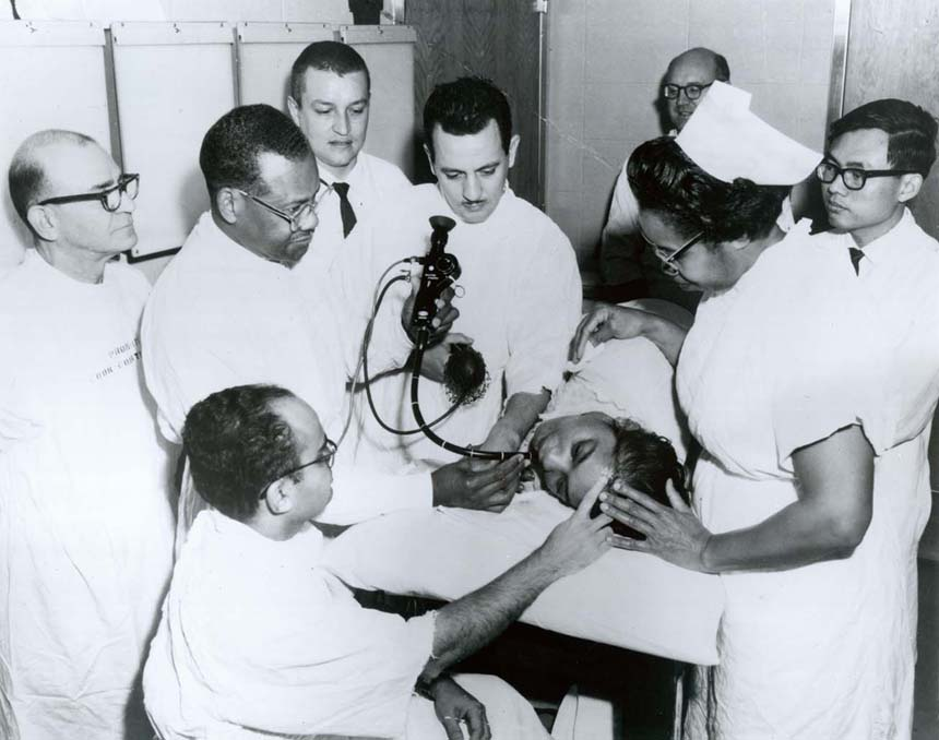 Dr. Berry using a medical instrument with a group of Cook County Residents and Postgraduate students. Handwriting on back.