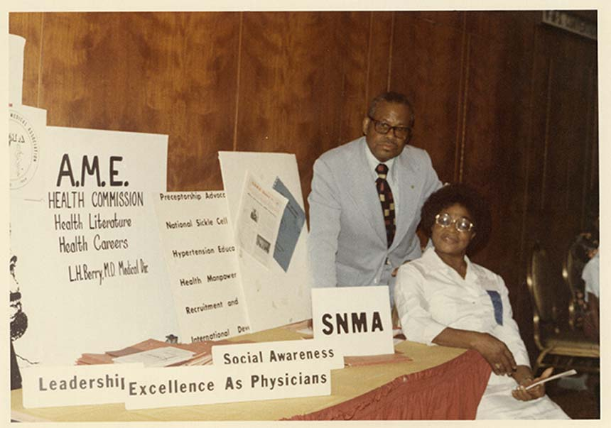 Dr. Berry standing behind a woman next to a table with AMA posters and literature.