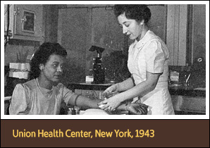 Standing White female nurse holds the arm of a seated African American woman.