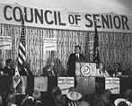 President Kennedy speaks at podium, flanked by 14 seated dignitaries, as a crowd looks on.