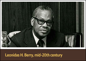 African American Man Leonidas Berry Seated At Desk And Looking Viewer