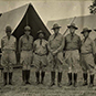 Photo of soldiers in uniform with hats and boots standing in a line in front of outdoor camp tents.