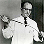 A man in a lab coat holding a long instrument with tubing in both hands.
