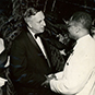 Dr. Berry in formal attire shaking hands with a white man and woman.