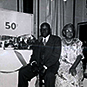 "African American male and female sharing a seat in a room with presents and a long table. ""50th"" on the board behind the table."