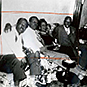 Three African American males and one female, smiling, sitting on a couch with arms around each other.