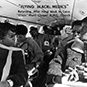 African American men and women seated on a plane.