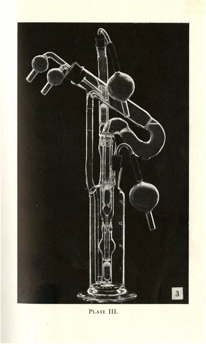 Tall, narrow, glass instrument with curved, cylindrical pipes and valves.