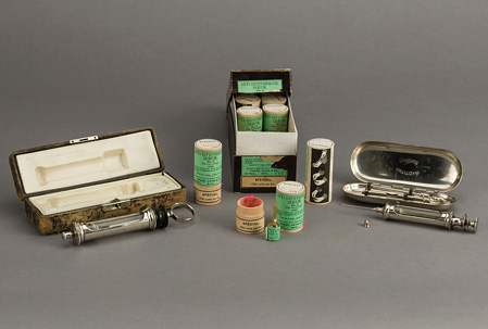 Box of wood canisters with green labels; small glass serum ampule is next to one open canister; two serum syringes with their cases are displayed on either side of box.
