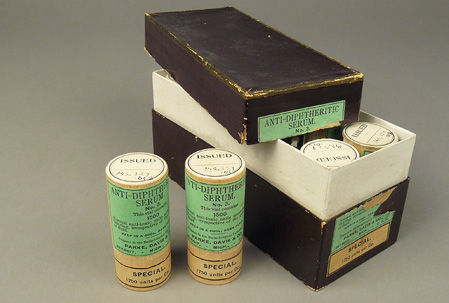Open box showing tops of small wood canisters inside; two green labeled canisters are next to the box.
