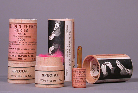 Three pink labeled wood canisters; one canister is open and glass serum ampule is next to it.