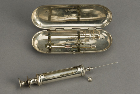 Metal serum syringe with needle attached is next to a metal case with hinged lid open.