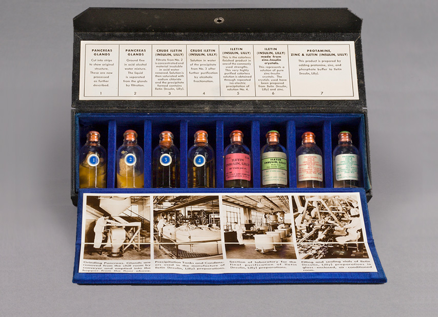 Opened rectangular sales kit with eight glass vials of insulin and includes labels and photographs