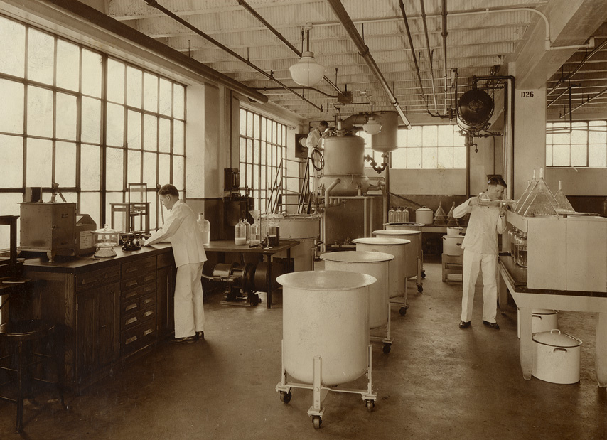 A man standing by a tall desk, and another man looking into one of four vats on wheeled frames.