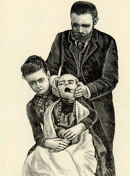 Front view of a seated woman holding a child in her lap; a man stands behind her holding the child's head; a tool holds the child's mouth open.