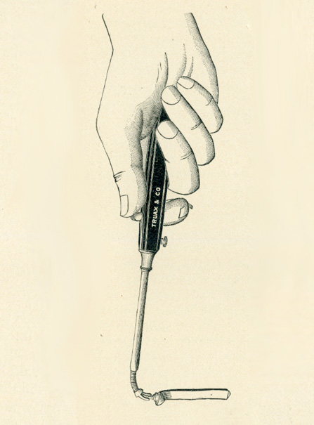 A hand holding a long tool with the thumb placed on a notch on its handle with elongated neck that curves down on its end where a tube is attached.