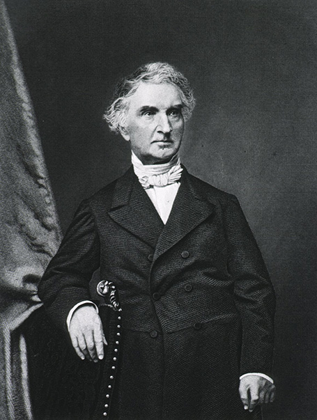 Half-length portrait of a man standing with the right arm over back of a chair.