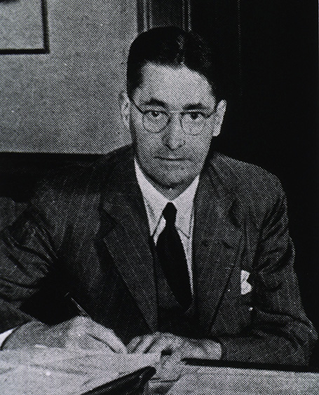 Black-and-white photo of Florey at a desk up which there are some papers.
