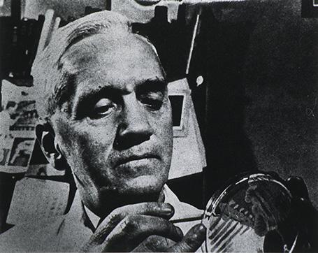 Black-and-white photo of Fleming holding up and probing a petri dish.