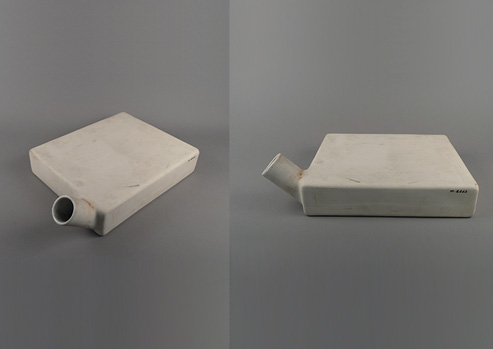 Square-sided, flat ceramic vessel with short cylindrical spout near one corner shown from the top and side.